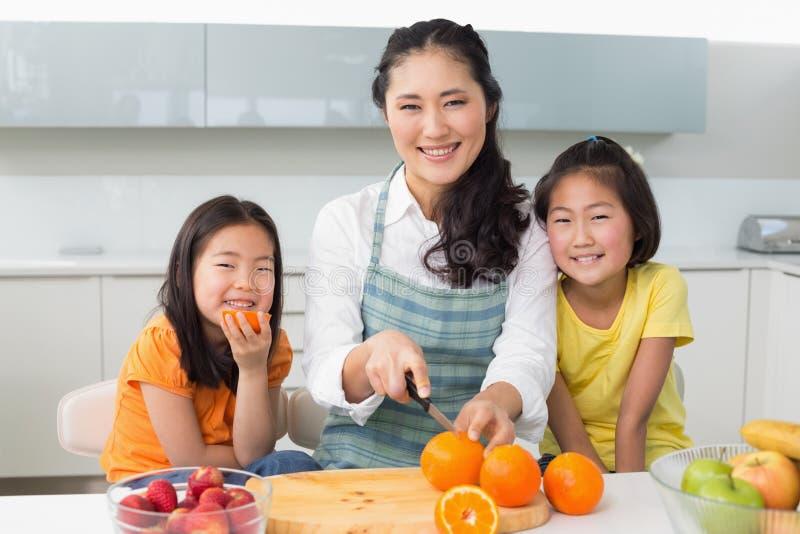Mulher com as duas filhas felizes que cortam o fruto na cozinha foto de stock