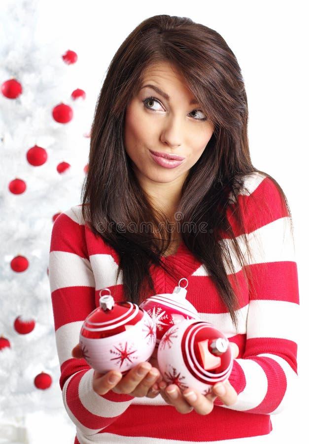 Mulher com as esferas ao lado da árvore de Natal foto de stock