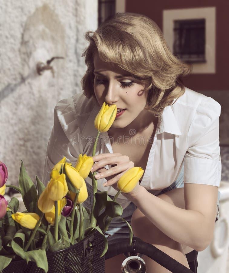 Mulher com as flores na bicicleta fotografia de stock