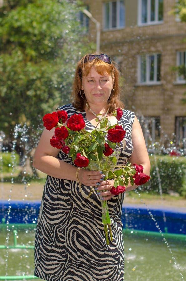 Mulher com as flores na fonte fotos de stock