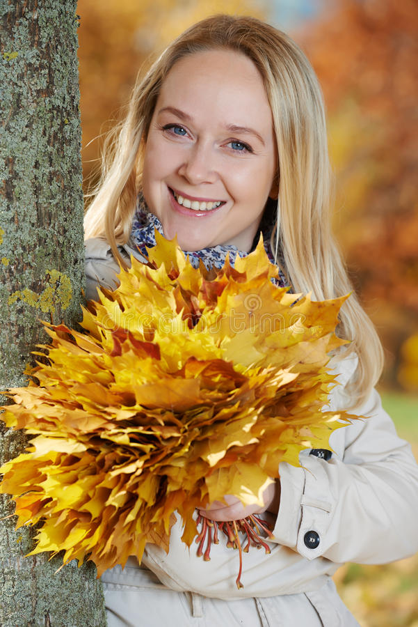 Mulher com as folhas de bordo no outono foto de stock royalty free
