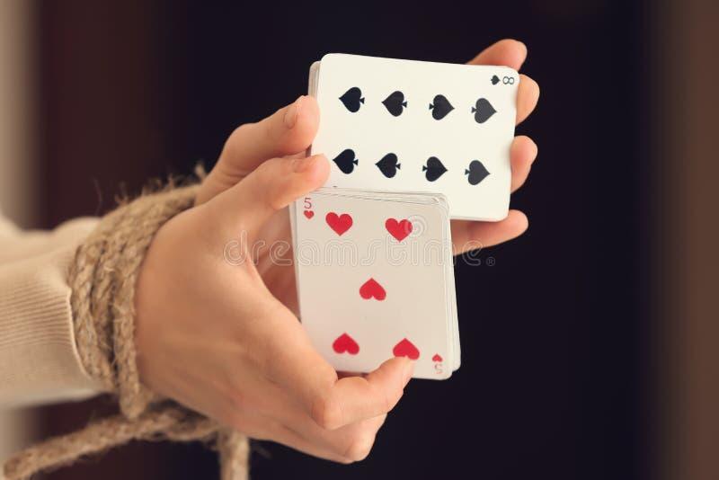 Mulher com as mãos amarradas que guardam cartões de jogo, close up fotos de stock