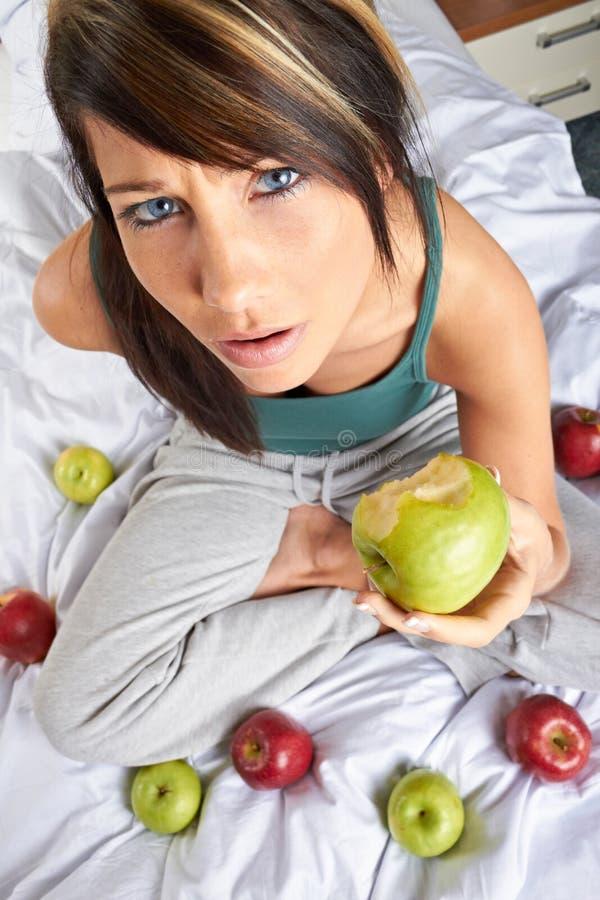 Mulher com as maçãs na cama fotos de stock royalty free