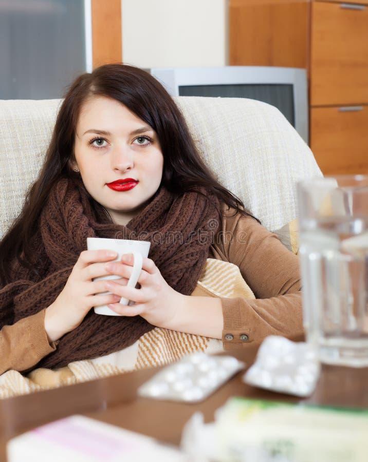 Mulher com as medicamentações na sala de visitas imagens de stock royalty free