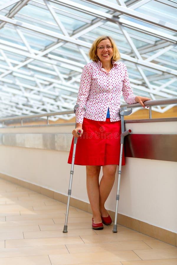 Mulher com as muletas que estão no hospital fotos de stock
