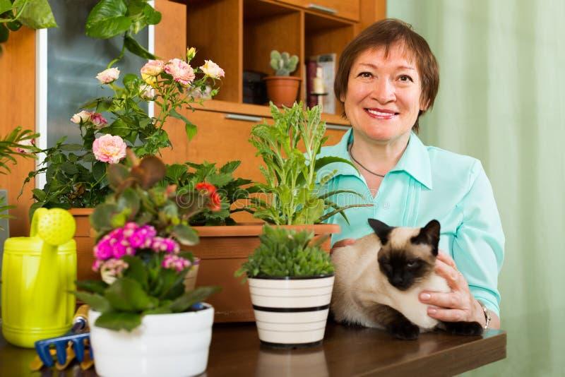 Mulher com as plantas do gato e da flor imagem de stock royalty free