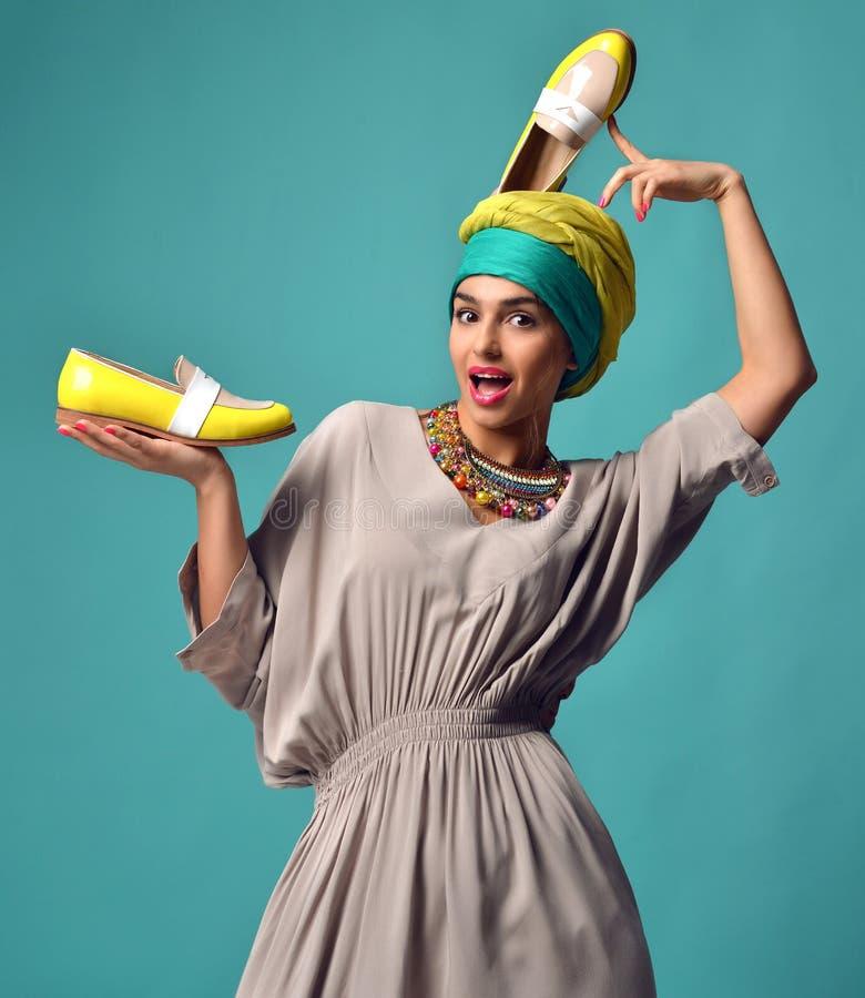 Mulher com as sapatas azuis e amarelas na cabeça e no tratamento de mãos dos pregos imagens de stock royalty free
