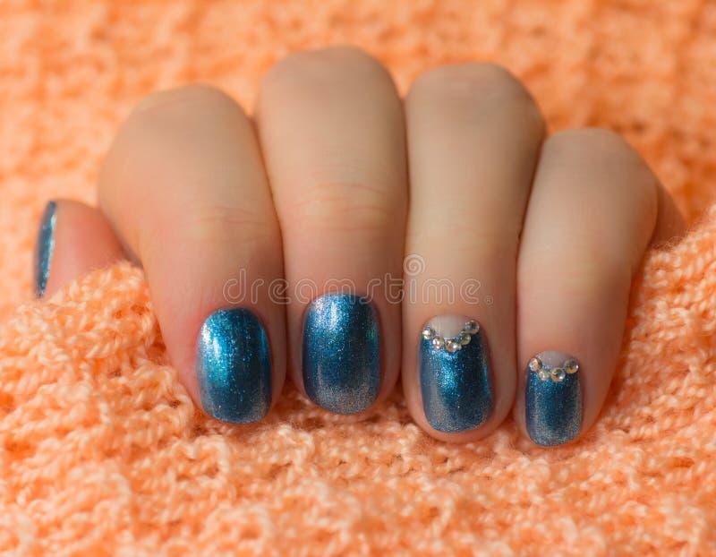Mulher com as unhas azuis manicured bonitas que cruzam graciosamente suas mãos para indicá-las ao visor em um fundo branco fotos de stock