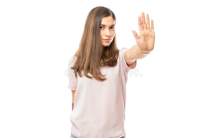 Mulher com a atitude má que faz o gesto da parada com sua palma imagem de stock royalty free