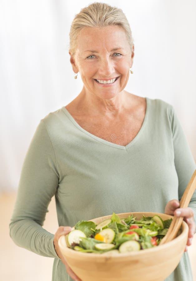 Mulher com a bacia de salada em casa imagens de stock