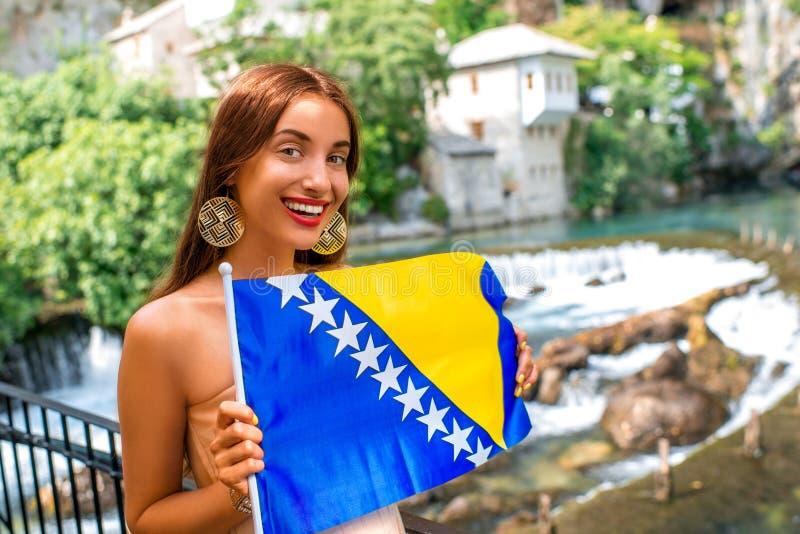 Mulher com a bandeira bosniana na vila de Blagaj fotografia de stock royalty free