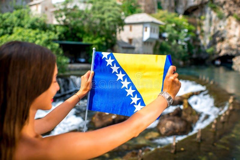 Mulher com a bandeira bosniana na vila de Blagaj imagens de stock
