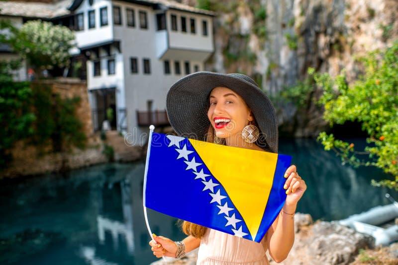 Mulher com a bandeira bosniana na vila de Blagaj imagens de stock royalty free