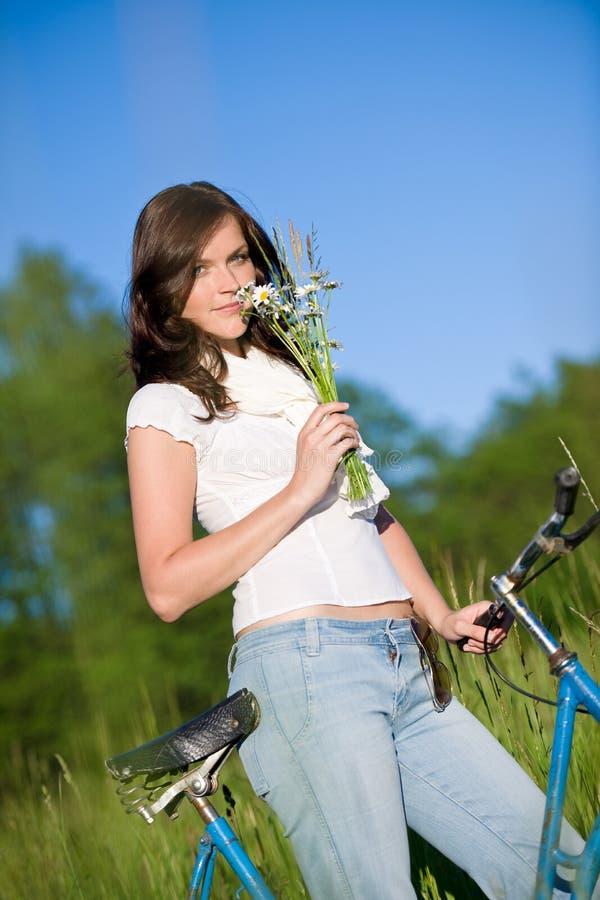 Mulher com bicicleta antiquado e flor do verão fotografia de stock royalty free