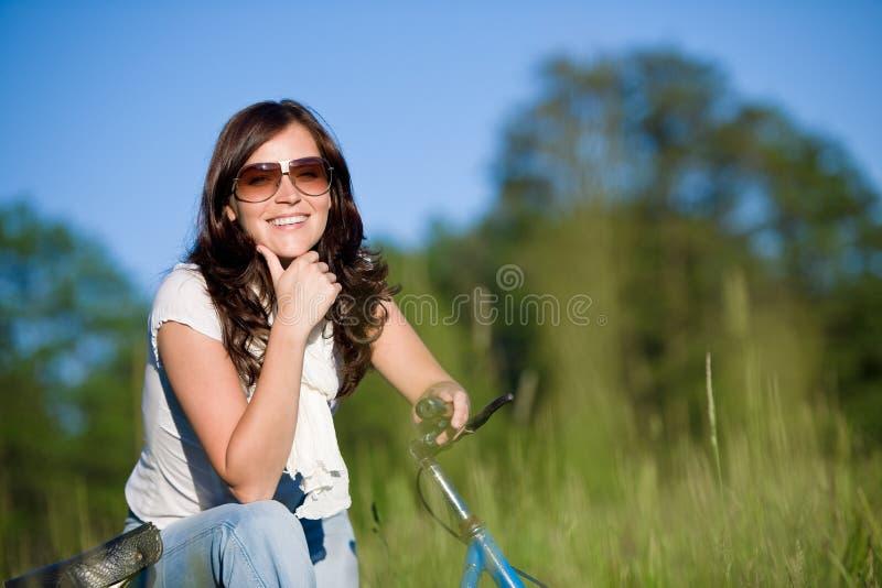 Mulher com a bicicleta antiquado no prado imagens de stock