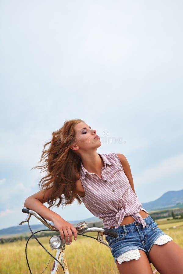 Mulher com bicicleta do vintage em uma estrada secundária fotos de stock