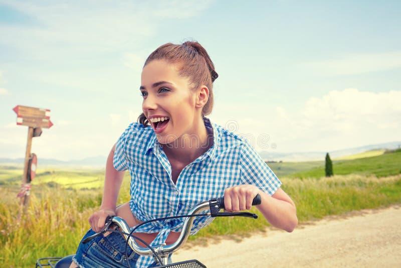 Mulher com bicicleta do vintage em uma estrada secundária fotografia de stock