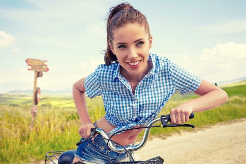 Mulher com bicicleta do vintage em uma estrada secundária imagem de stock