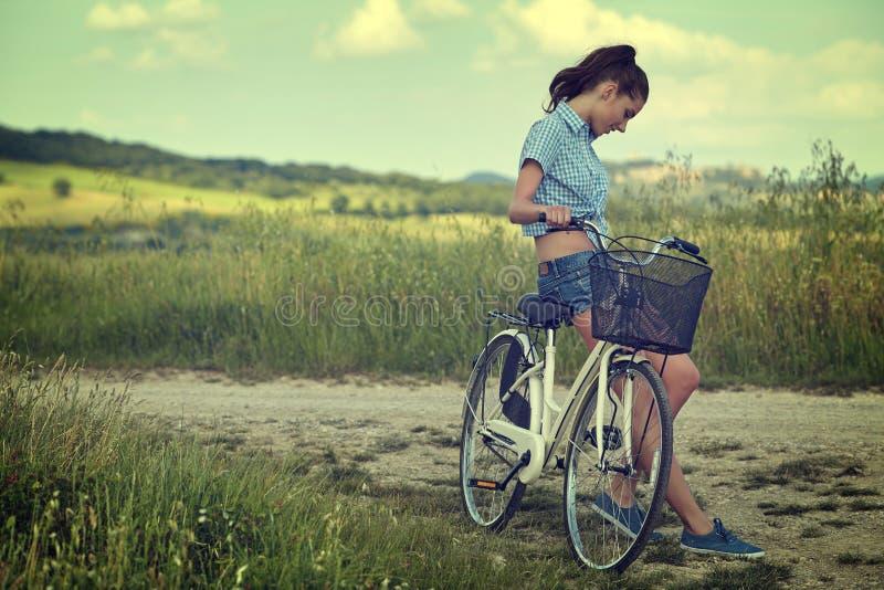Mulher com bicicleta em uma estrada secundária fotografia de stock