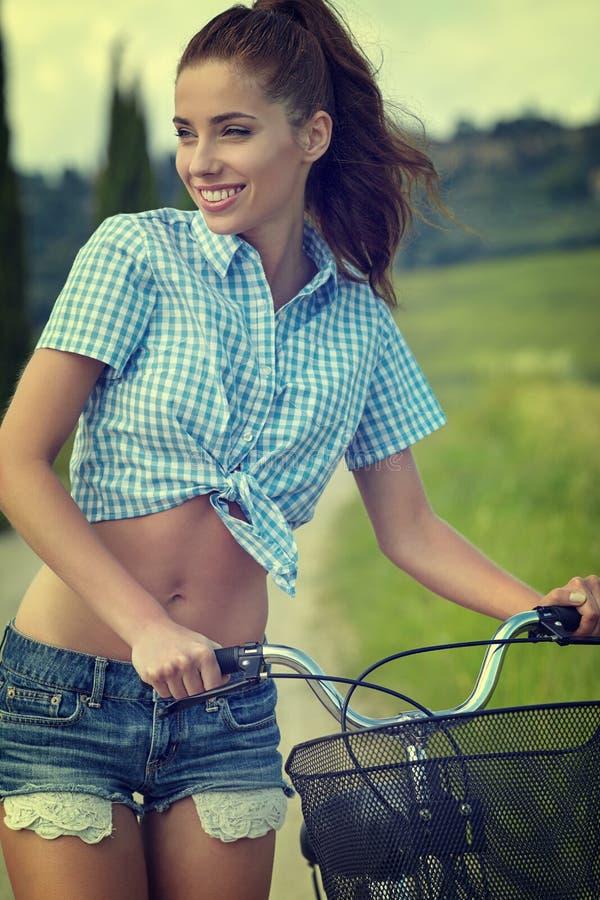 Mulher com bicicleta em uma estrada secundária imagens de stock royalty free