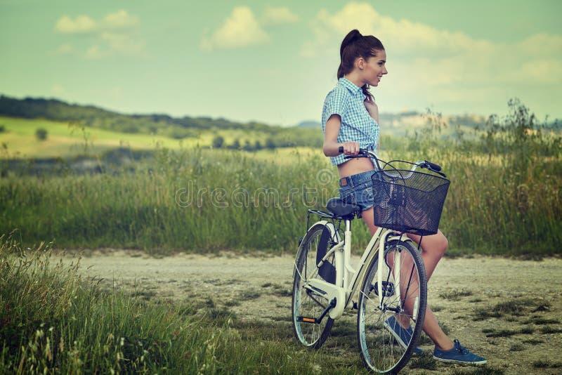 Mulher com a bicicleta exterior, verão Toscânia do vintage imagem de stock royalty free