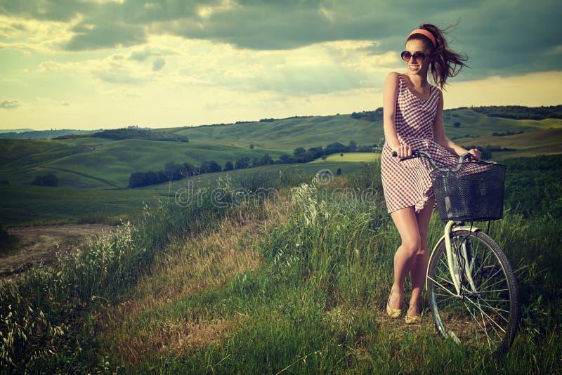 Mulher com a bicicleta exterior, verão Toscânia do vintage fotos de stock royalty free