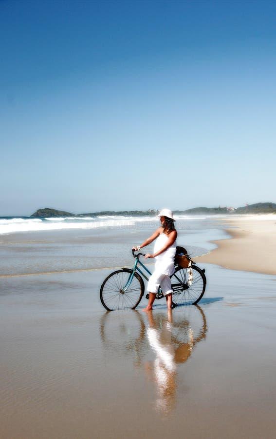 Mulher com a bicicleta na praia