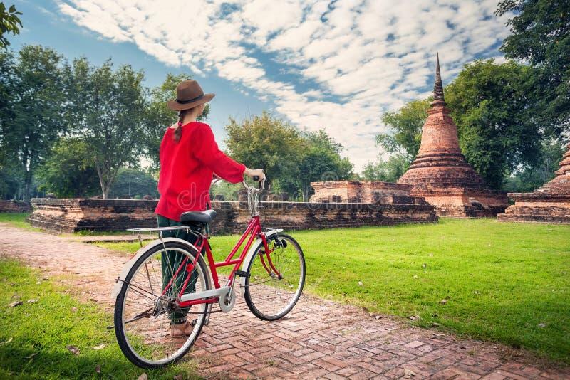 Mulher com a bicicleta perto das ruínas budistas imagem de stock royalty free