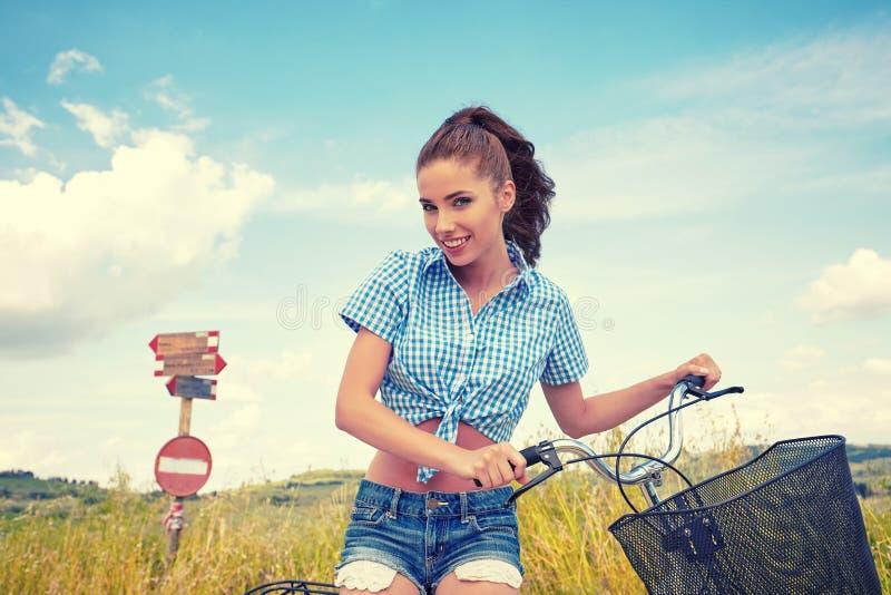 Mulher com a bicicleta que está na estrada e que olha a em algum lugar imagens de stock royalty free
