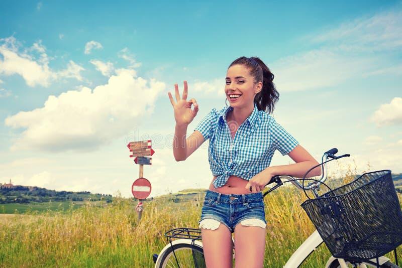 Mulher com a bicicleta que está na estrada e que olha a em algum lugar foto de stock