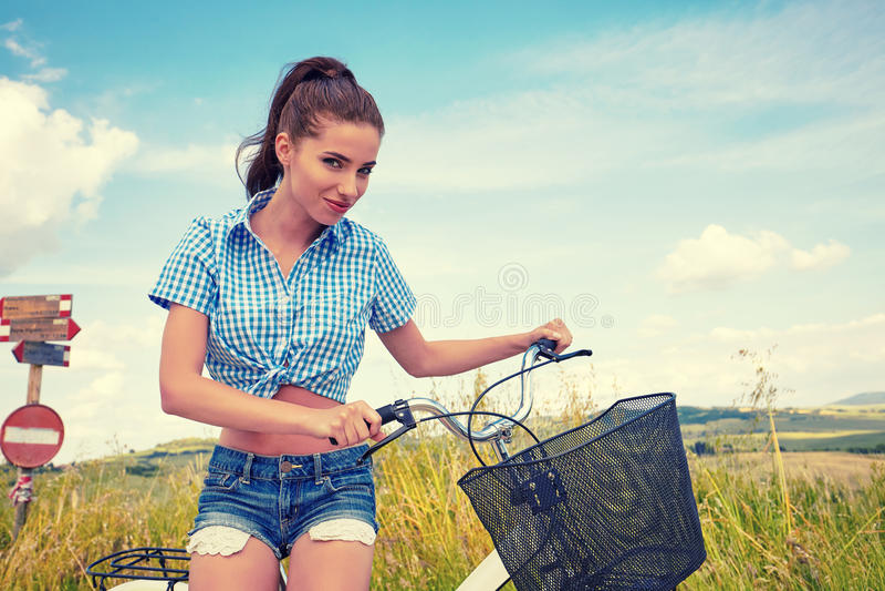 Mulher com a bicicleta que está na estrada e que olha a em algum lugar fotos de stock