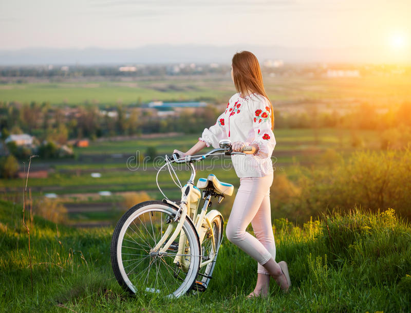 Mulher com a bicicleta retro no monte na noite fotos de stock