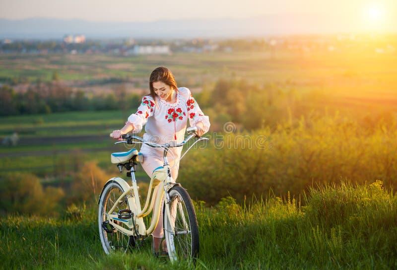 Mulher com a bicicleta retro no monte na noite foto de stock