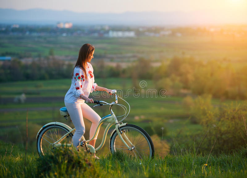 Mulher com a bicicleta retro no monte na noite foto de stock royalty free
