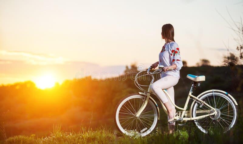 Mulher com a bicicleta retro no monte na noite imagem de stock royalty free