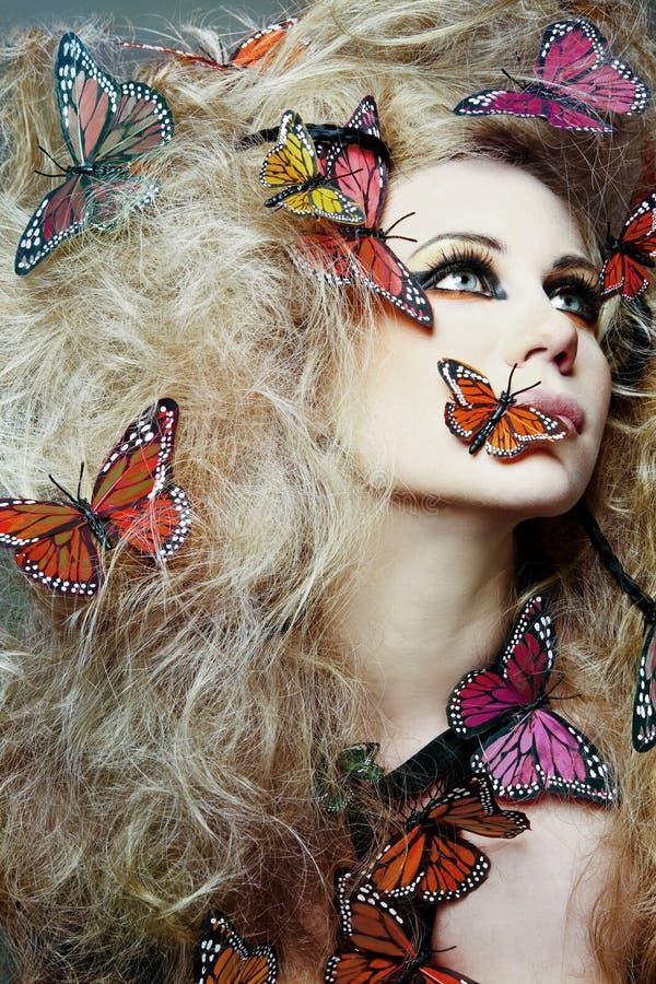 Mulher com a borboleta no cabelo curly. imagem de stock royalty free