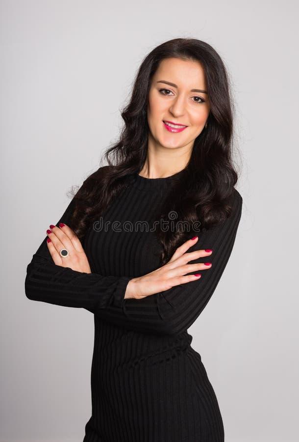 A mulher com braços cruzou-se contra um fundo da parede cinzenta fotos de stock