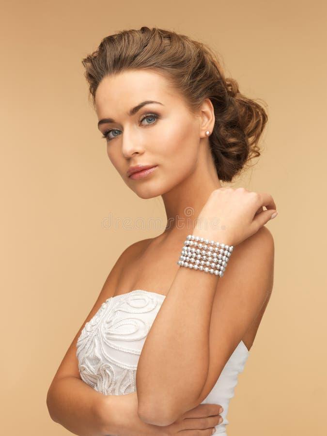 Mulher com brincos e bracelete da pérola imagem de stock