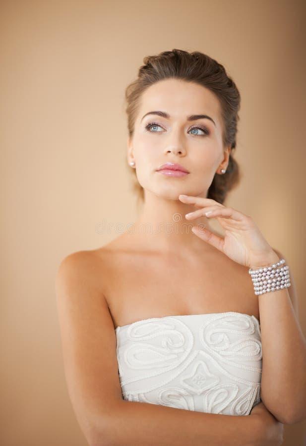 Mulher com brincos e bracelete da pérola imagens de stock