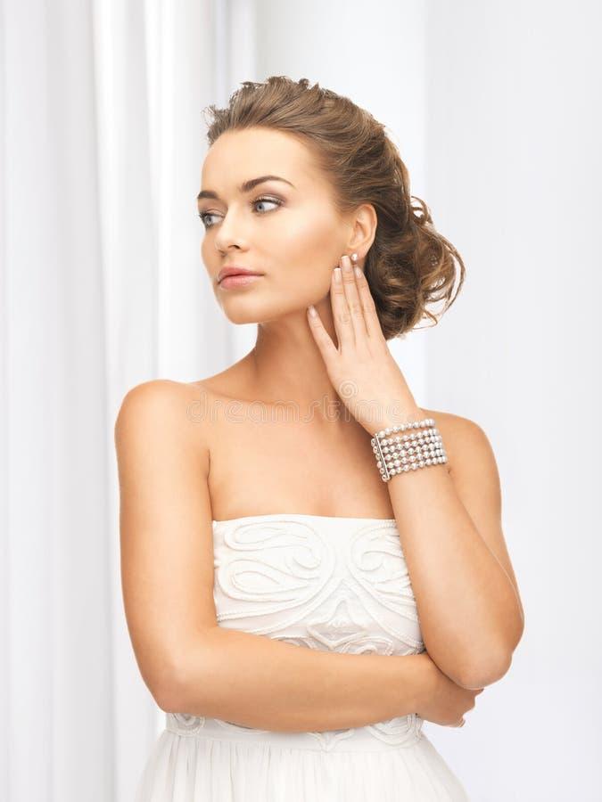 Mulher com brincos e bracelete da pérola fotos de stock