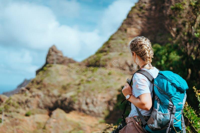 Mulher com câmera e trouxa na frente das aletas áridas das rochas na ilha de Santo Antao, Cabo Verde fotografia de stock