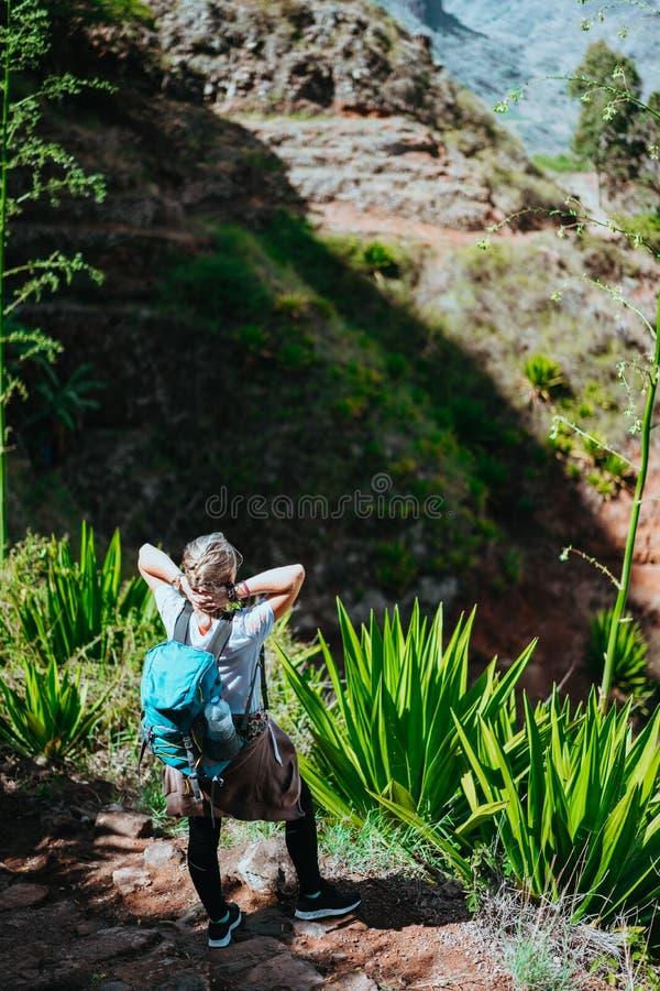 Mulher com câmera e trouxa na frente das aletas áridas das rochas na ilha de Santo Antao, Cabo Verde foto de stock