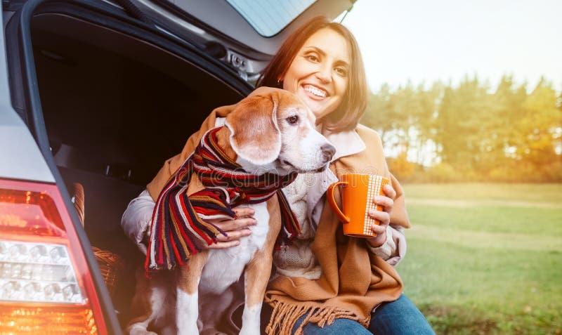 A mulher com cão senta-se junto no caminhão do gato e aquece-se o chá quente do ???? Auto curso com imagem do conceito dos animai fotos de stock