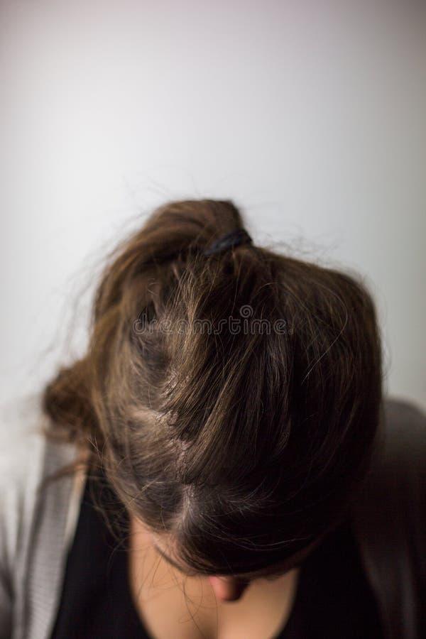 Mulher com a cabeça inclinada contra o fundo branco fotografia de stock royalty free