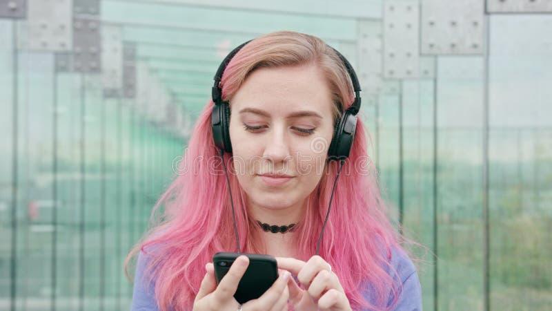 Mulher com cabelo cor-de-rosa usando um telefone na cidade fotografia de stock