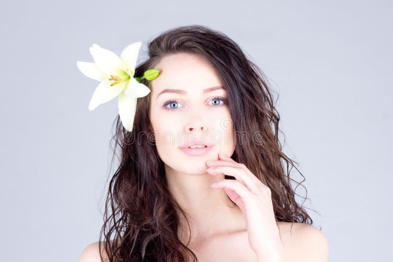 Mulher com cabelo encaracolado e os olhos azuis grandes que tocam nos bordos Mulher com uma flor em seu cabelo foto de stock royalty free