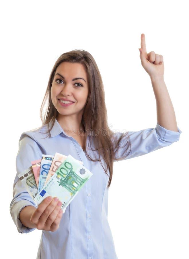 Mulher com cabelo escuro e dinheiro longos que aponta acima fotografia de stock royalty free