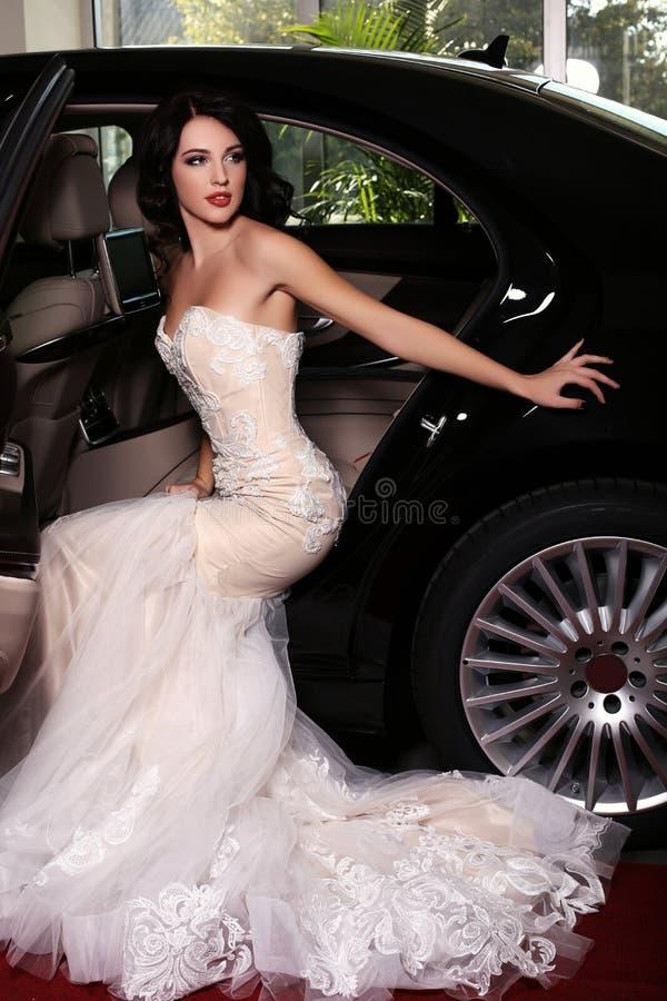 A mulher com cabelo escuro veste o vestido luxuoso, chegado no evento do tapete vermelho fotografia de stock