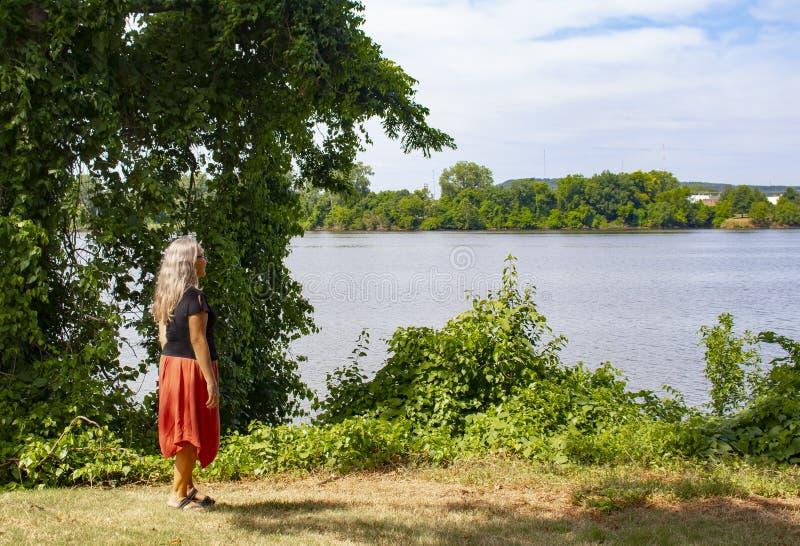 A mulher com cabelo louro cinzento longo vestiu-se na saia e na blusa que estão no banco do rio que olha para fora através dele imagens de stock royalty free