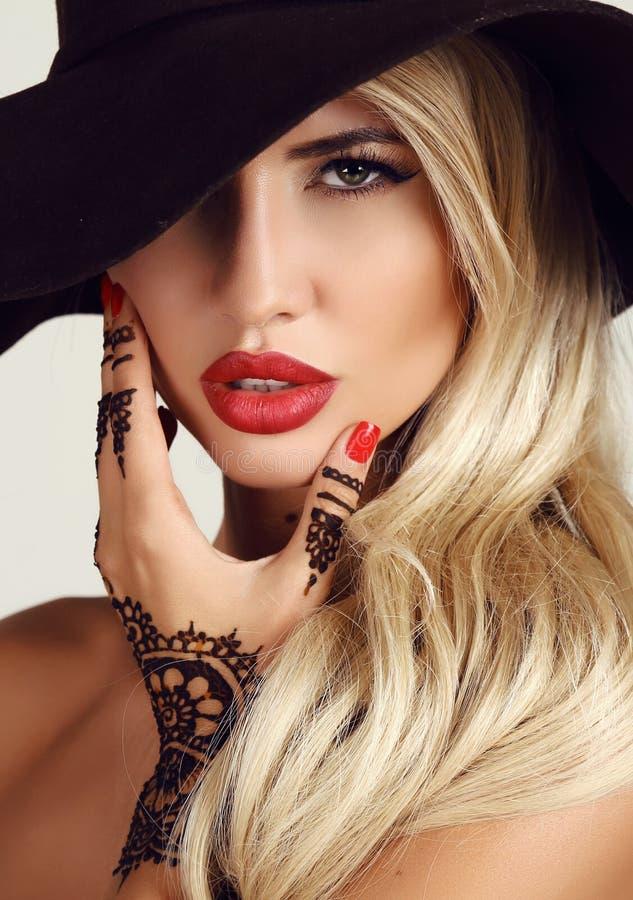 Mulher com cabelo louro com composição da noite e tatuagem da hena nas mãos foto de stock